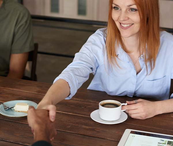 A white woman sitting at a table shakes hands with a Black man.